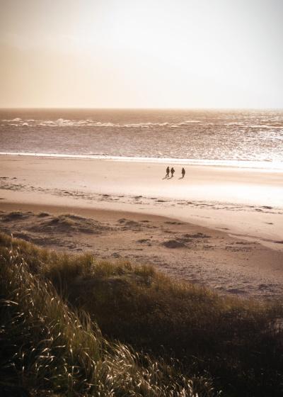 Tre mennesker går på Blåvandshuk strand med solen i baggrunden.