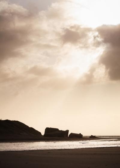 Tyske bunkere ved vandet med solstråler igennem skyerne.