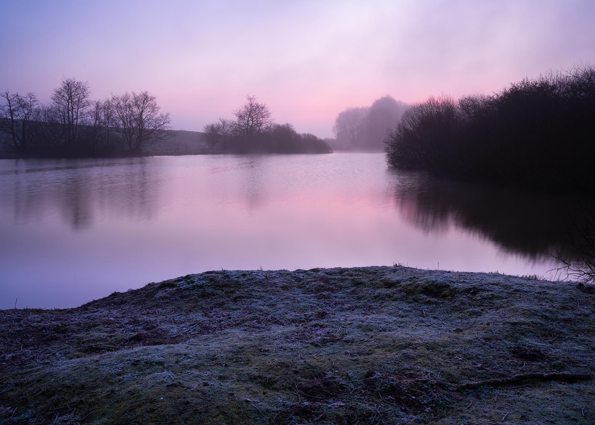 Udsigt over en stille sø, med dis i baggrunden, og røde nuancer i himlen.